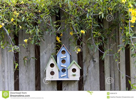 colorful birdhouses   fence  yellow flowers