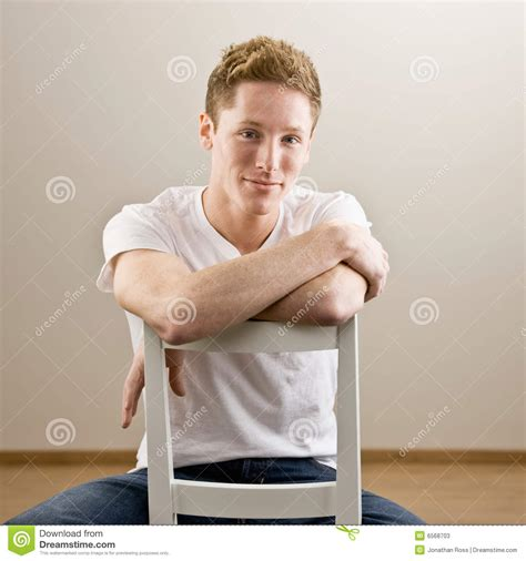 young man sitting   chair stock  image