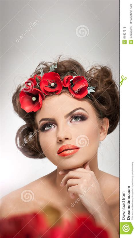 Portrait Of Beautiful Girl In Studio With Red Flowers In