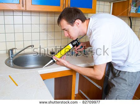 what kind of caulk for kitchen sink plumber putting a silicone sealant to installing a kitchen