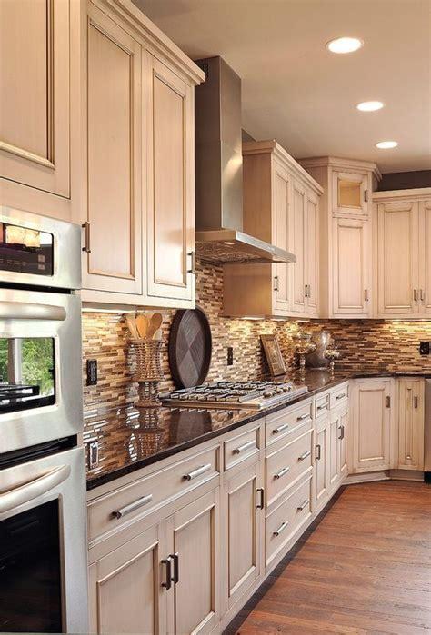 stacked stone backsplash  white cabinets  hardwood