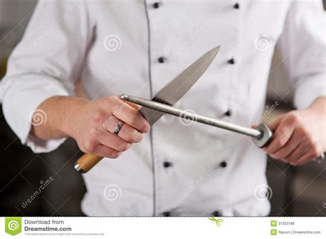 chef sharpening knife in commercial kitchen stock photo