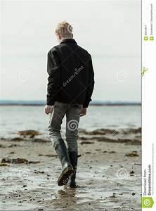 Young Man Walking Alone On Beach Stock Photo - Image: 85872817