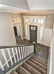 Entryway with gray stair rail and white ballusters