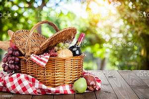 Picnic, Basket, On, A, Wooden, Table, Against, Defocused, Lush, Foliage, Stock, Photo
