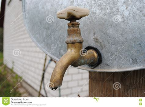Vintage Old Brass Water Tap On A Galvanized Water Tank