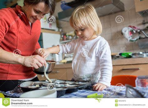 et sa cuisine aide de fille de bébé faisant cuire avec sa maman dans la