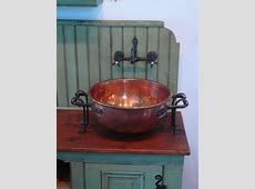 The sink is an antique copper candy kettle with wrought