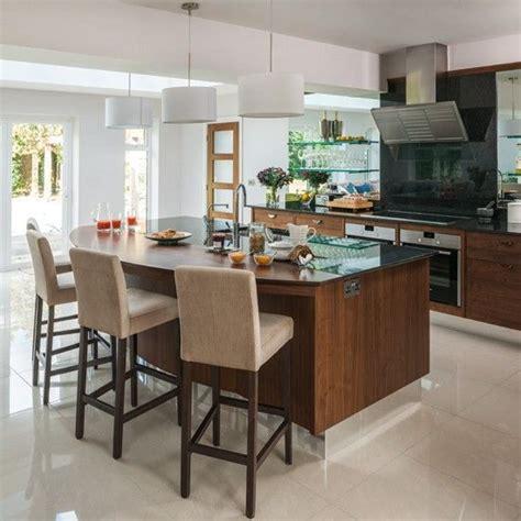 Modern glass and walnut kitchen with breakfast bar