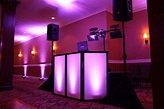 DJ setup with facade and purple uplighting provided by All ...