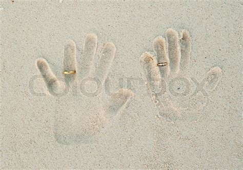 print of with wedding rings on sand wedding