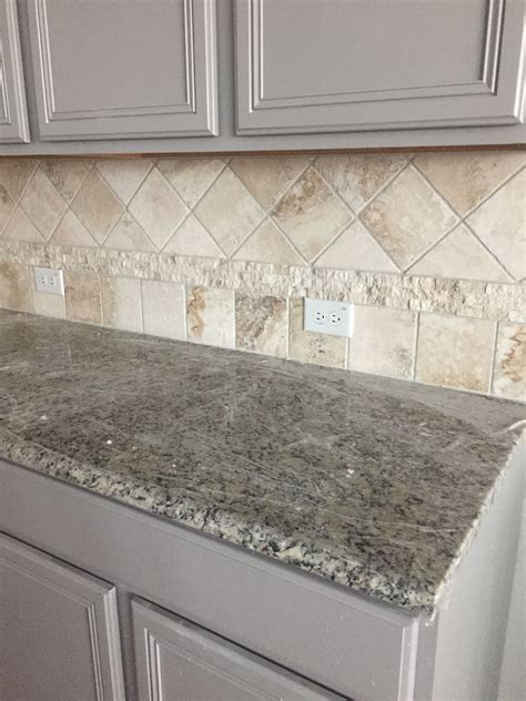 Gray kitchen cabinets, travertine backsplash, Santa