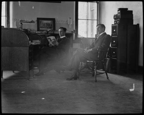 Two Men Sitting In A Office Reading Gee Lindquist