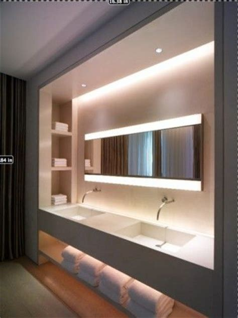 a custom built wall mounted vanity unit with cove lighting shelf niches and a expanse of