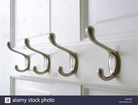 Chrome Coat Hooks Are Mounted On The Back Of A Closet Door