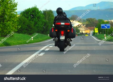 Motorcycle Rider Riding Down A Lonely Country Road Stock