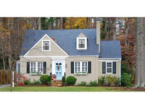 tan taupe house black shutters blue door  board