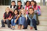 A group of elementary school kids sitting on school steps ...