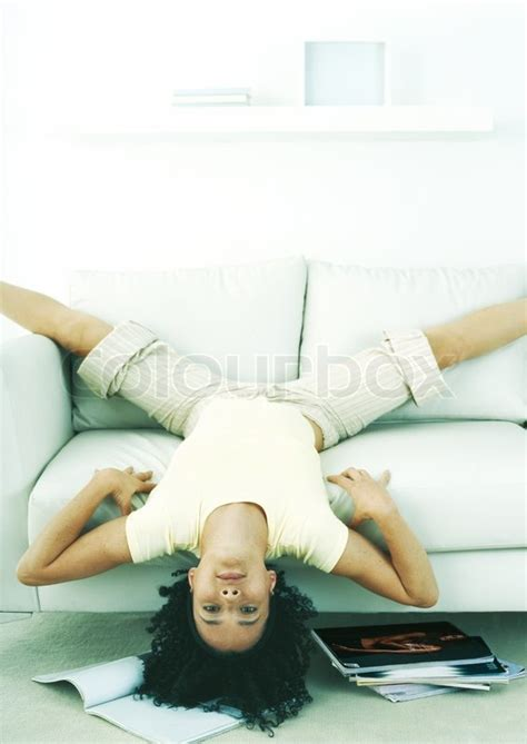 One Person Sofa by Woman Hanging Upside Down Off Edge Of Sofa Stock Photo