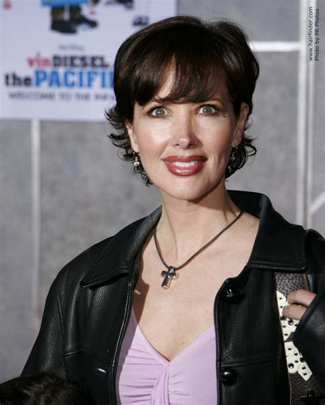 Janine Turner sporting short hair with layers springing up in the back