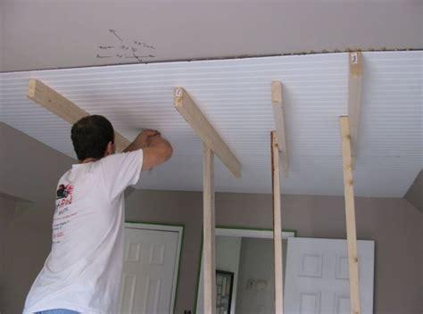 interior worker installing beadboard ceiling panels