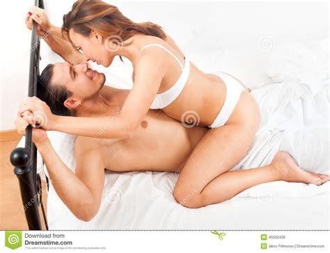 Happy Adult Couple Having Sex On Bed In Bedroom Interior