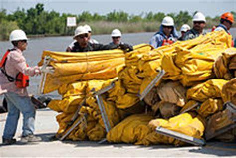 men  hard hats standing  water   large pile