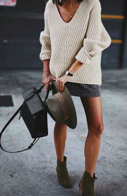 of a neutral low cut sweater a grey mini skirt green suede boots and a black bag