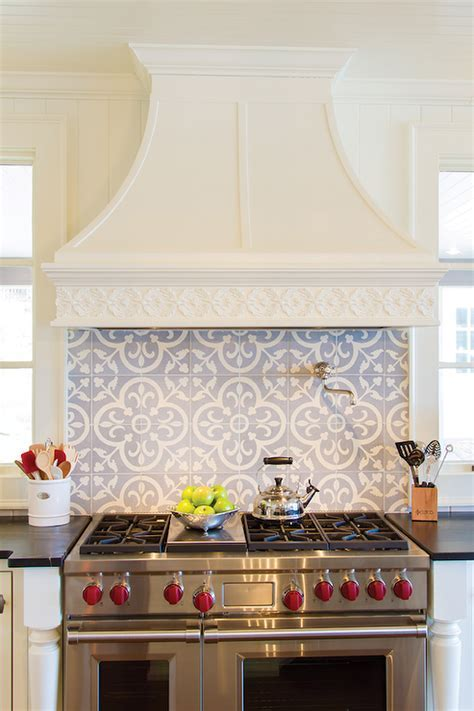 Stunning kitchen features an ivory French range hood