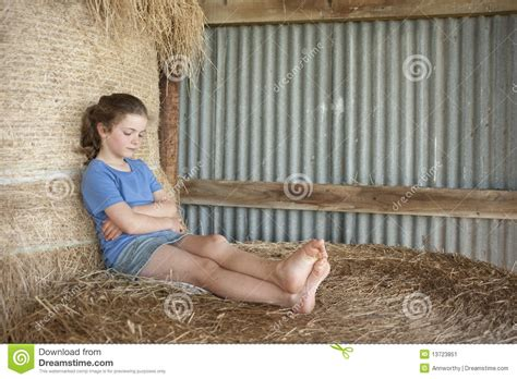 Little Girl Relzxing On Bales Of Hay In Barn Stock Image