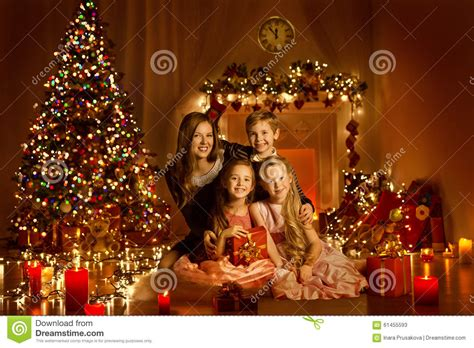 family in decorated home room tree