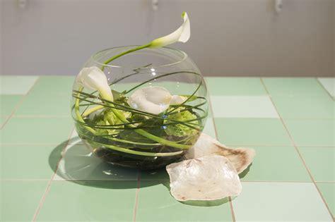 kugelvase dekoriert mit calla nelken und schwimmpflanzen
