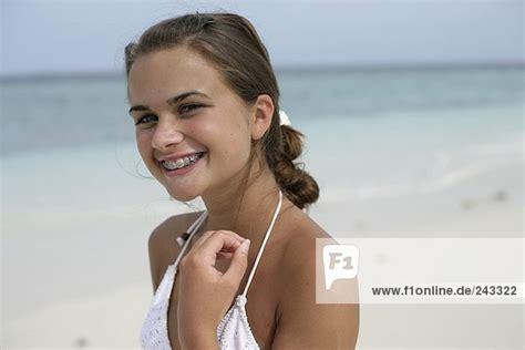 junges maedchen  strand lacht  kamera traegt zahnspange