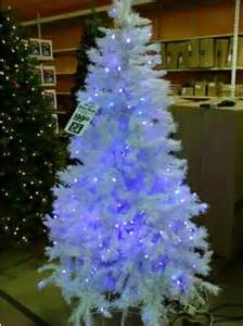 white tree with blue lights happy holidays