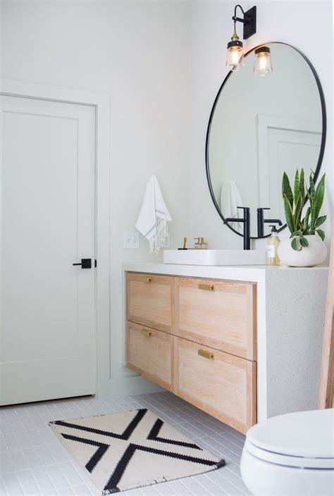 big round mirror in bathroom with white oak vanity and