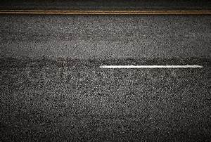 Road marking: white and yellow lines on the dark asphalt ...