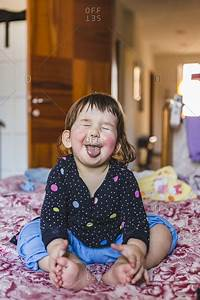 Portrait, Of, Toddler, Sitting, Barefoot, On, Bed, Sticking, Out, Tongue, Stock, Photo