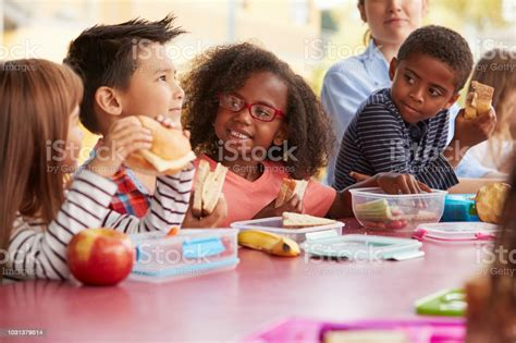 young school kids eating lunch talking   table