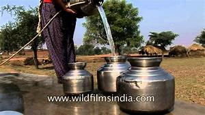 Villagers collecting water from bore well using a pulley ...