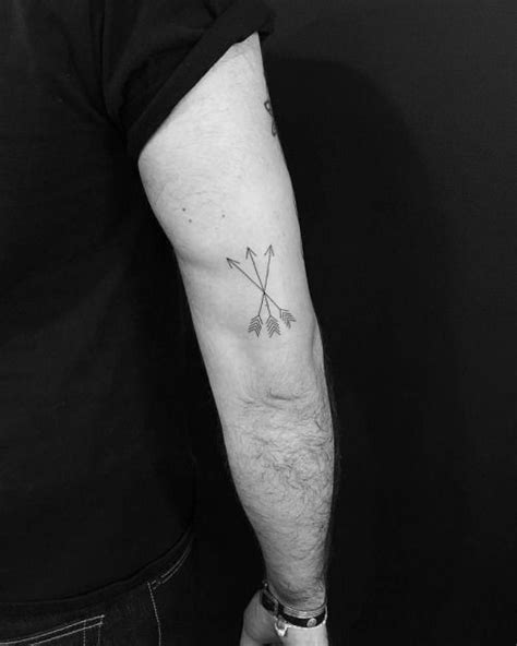 Three arrows tattoo on the back of the right arm. Tattoo