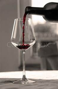 Pouring red wine from bottle into ... | Stock Photo ...