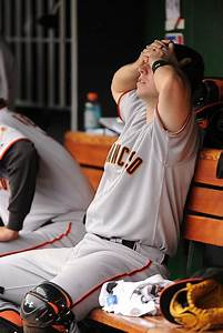 Cutie Giants catcher Buster Posey hides his eyes during a