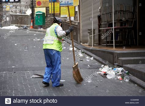female street cleaner brushing streets  broom early
