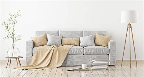 empty white wall mockup with sofa pillows plaid and lamp