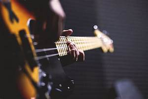 Person Playing Sun Burst Electric Bass Guitar in Bokeh ...