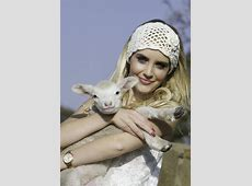 Pretty Blonde Woman With White Crochet Headband Holding