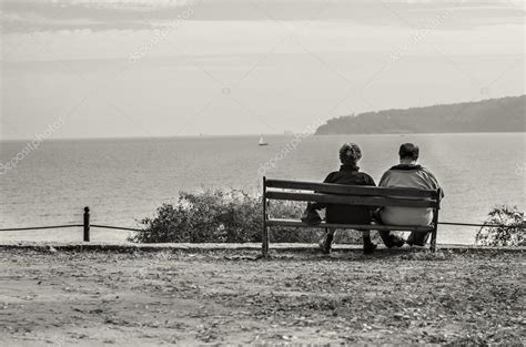 Old Couple Sitting On Bench Watching The Ocean — Stock