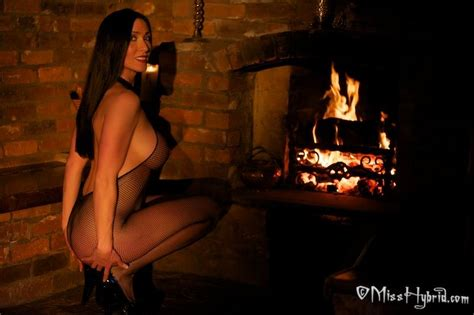 Sexy Milf Miss Hybrid Poses In Front Of A Fireplace