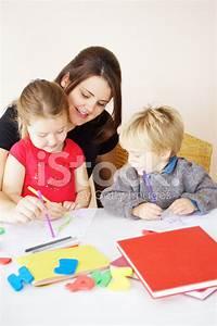 Mother OR Teacher Helping Little Children stock photos ...