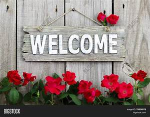 Rustic welcome sign hanging on wood fence with flower